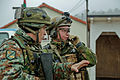 A Macedonian soldier speaks with a Norwegian soldier during a military adviser team (MAT) and police adviser team (PAT) training exercise at the Hohenfels Training Area, a part of the Joint Multinational 131213-A-HJ139-002.jpg