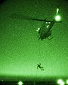 A U.S. Marine rappels from a UH-1N Huey helicopter. (9087077004).jpg