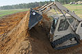 A U.S. Soldier with the 131st Engineer Company uses a Skid Steer to dig out vehicle fighting positions from a burm, to provide a solid defense for the brigade command post against mock apposing forces during 140621-Z-HS490-003.jpg