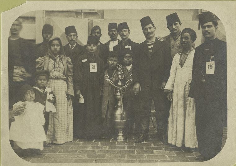 A group of immigrants, most wearing fezzes