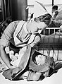 A nurse places a crying baby into its gas respirator during a drill at a London hospital in 1940. D651.jpg