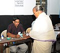 A polling official administering indelible ink to a voter, at a polling booth, during the Puducherry Assembly Election on May 16, 2016.jpg