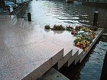 Photo en couleurs (teinte bleutée dominante), prise à Amsterdam en novembre 2003, et montrant le «Homomonument»: un monument dédié aux victimes homosexuelles du nazisme. La photo en montre seulement une partie: un assemblage de cinq dalles en granit rose qui forment un escalier triangulaire permettant d'accéder, du trottoir, au bord d'un canal (de gauche à droite sur la photo). La dernière marche, une plate-forme triangulaire, qui semble flotter sur l'eau du canal, est en partie recouverte de gerbes de fleurs. L'arrière-plan de la photo est constitué par l'étendue d'eau du canal.