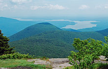 A view from a rocky mountain ledge over a lower mountain to a distant, winding lake