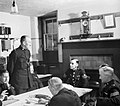 At Wotton-under-Edge police station, Sergeant Auger (seated at the head of the table) chats to some of the twenty-two Special Constables who have joined the three regualrs in keeping law and order in the town, 1944. D22047.jpg