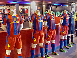 A number of jerseys, footballs and other association football equipment inside FC Barcelona's sports store.