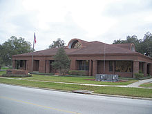a fairly large one story brick building with a flagpole and a sign saying 'Bartow City Hall' in front