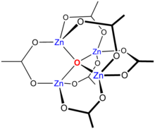 Skeletal chemical formula of a three-dimensional compound, featuring oxygen atom in the center, bonded to four Zn atoms. The latter are interconnected through oxygens and O-C-O groups.