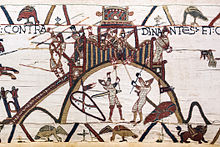 A section of an embroidered cloth showing a castle on a hilltop being defended by soldiers with spears while two soldiers in armour are attempting to set fire to the palisade