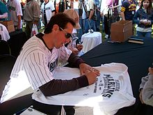 A young dark-haired man with sunglasses writing on a baseball jersey