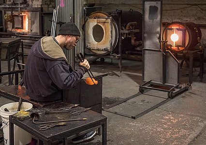 A man working on a glass project after removing it from a kiln at Brooklyn Glass.