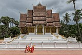 Buddhist monks walking in front of the temple Haw Pha Bang in Luang Prabang.jpg