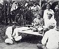 COLLECTIE TROPENMUSEUM Mensen bijeen rond een bank van bamboe onder wie een vrouw met kind aan de borst Nederlands-Indië TMnr 60040117.jpg