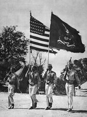 Color guard of four Filipino men wearing World War II United States Army Uniform; the national colors and regimental colors in the center.