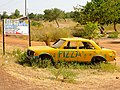 Car and hoarding advertising a pizza restaurant in Burkina Faso, 2009.jpg