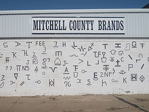Livestock branding - Cattle brands used in Mitchell County in West Texas are displayed on a public mural in Colorado City, Texas.