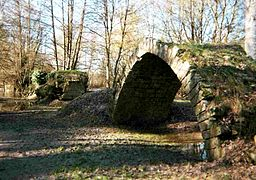 View of the ruined arch of a bridge isolated in a meadow
