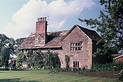 A stone house seen from a slight angle, with a gabled wing to the right and a tall chimney on the roof to the lefy