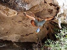 Un grimpeur agrippant dans un toit sur un bloc en extérieur et écartant les jambes pour accrocher ses pieds aux prises