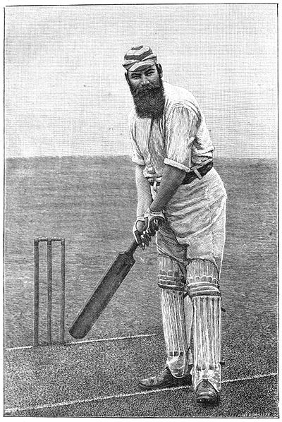 W.G. Grace (a tall man with a large bushy beard), dressed in cricket whites and holding a cricket bat in front of a wicket, left foot forwards