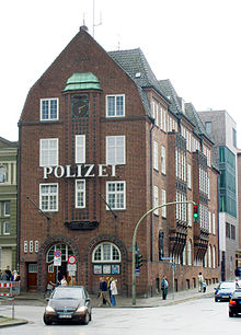 A 3 floor red-brick building, with the German word 'police' in large letters between first and second floor. The windows are white sash windows.