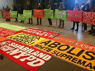 "image of banners on floor of museum lobby, reading ""Fuera Warren Kanders"" and ""Safariland Supports the NYPD"""