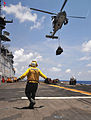 Defense.gov News Photo 110519-N-ZS026-132 - U.S. Navy Petty Officer 3rd Class Rodolfo Lopez signals an MH-60 Seahawk helicopter with Helicopter Sea Combat Squadron 23 to lower a pallet of.jpg