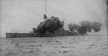 A large warship is partially obscured by smoke from its main guns firing