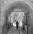 Doorkijkje door poort met daarin een oude man en dagelijkse bedrijvigheid, Bestanddeelnr 255-2442.jpg