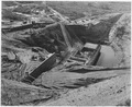 Downstream view from the right end of the spillway bucket showing concrete pouring operations on the crib cut-off... - NARA - 295316.tif