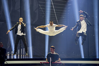 Two singers and an acrobat jumping on a trampoline