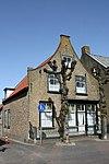 foto van Huis met ingezwenkte halsgevel van gele baksteen met vernieuwde rollaag