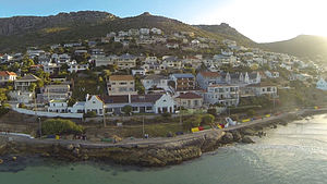 Fish Hoek - An aerial view from the ocean of the houses on the slopes in the southern part of Fish Hoek