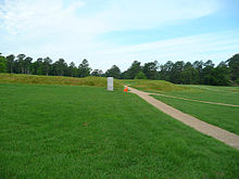 A wide grassy field with a paved walkway running through it. In the distance is a small stone marker.