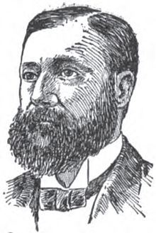 A man with dark hair and a bushy mustache and beard wearing a black jacket and tie and white shirt
