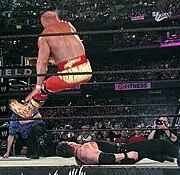 Hulk Hogan haciendo su Atomic Leg Drop en Vince McMahon en el suelo