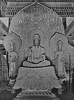 Front view of a central figure sitting cross-legged on a raised platform which is flanked by two smaller standing statues. The central figure has the palm of his right hand turned to the front. The attendants look identical pointing upwards with their right hand and their left hand lifted halfway touching the thumb with the middle finger. Each of the three statues has a halo.