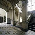Interieur, overzicht van het trappenhuis aan de smalle zijde van de hoofdentree, met zuilen, tegelvloer, een zandstenen balustrade en gewelven - 's-Gravenhage - 20387451 - RCE.jpg