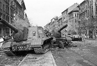 Two disabled Soviet ISU-152 assault guns in Budapest's 8th District with an abandoned T-34/85 tank in the background. Jozsef korut a Corvin (Kisfaludy) koznel. Harckeptelenne tett ISU-152-es szovjet rohamlovegek, a hatterben egy T-34-85 harckocsi. Fortepan 24854.jpg