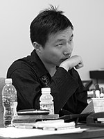 An Asian man in a dark shirt seated at a desk and looking right with his wrist held to his chin