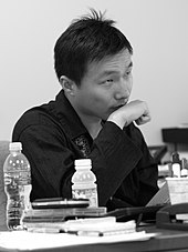 Black-and-white photo of an Asian man seated at a desk, holding his fist to his chin.