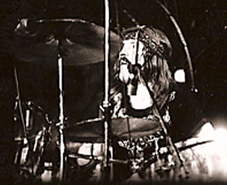 A black and white photograph of John Bonham wearing a headband and behind the cymbals of a drum kit