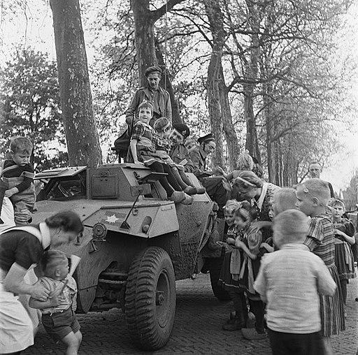 Kinderen (waarvan sommige in klederdracht) en verpleegster bij pantserwagen, Bestanddeelnr 900-2852