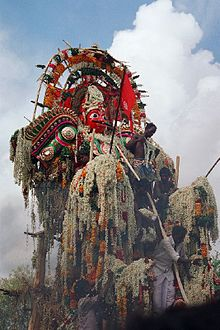 A huge sculpture of an armoured warrior man, with a moustache and red face. He is adorned with many floral garlands, which also cover his arms. Male priests surround him.