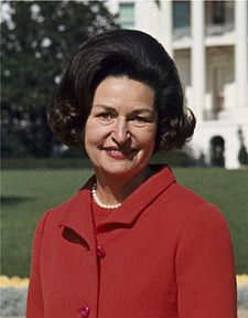 Lady Bird Johnson, photo portrait, standing at rear of White House, color, crop.jpg