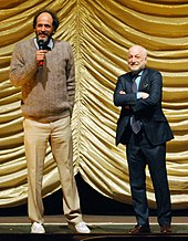 Two middle-aged Caucasian men stand before a yellow curtain on stage.