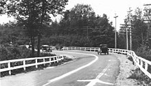 An old photograph of a bend in a road surrounded by trees and power poles. There are wooden guardrails on either side of the road, with a white-painted center line separating the two lanes of traffic. Two old cars are approaching the curve which also has arrows to denote the direction of traffic.
