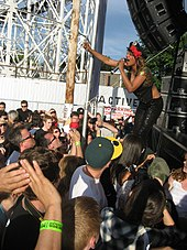 A dark-skinned woman wearing a black hat and black clothing holding a microphone while performing on stage to a crowd of people. The performance is taking place outdoors and part of a rollercoaster is visible in the background.