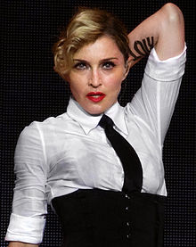 A middle-aged blond woman looking towards the camera. She wears bright, red lipstick and has her left hand behind her head