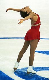 A female ice skater in white boots and a red dress